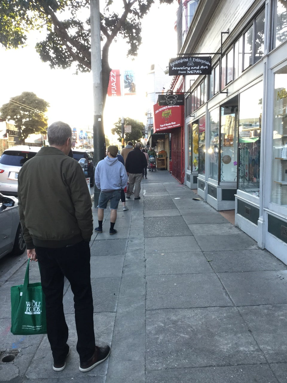 Line of people on the sidewalk on Haight street, about six feet apart, waiting to get into Haight Street Market.