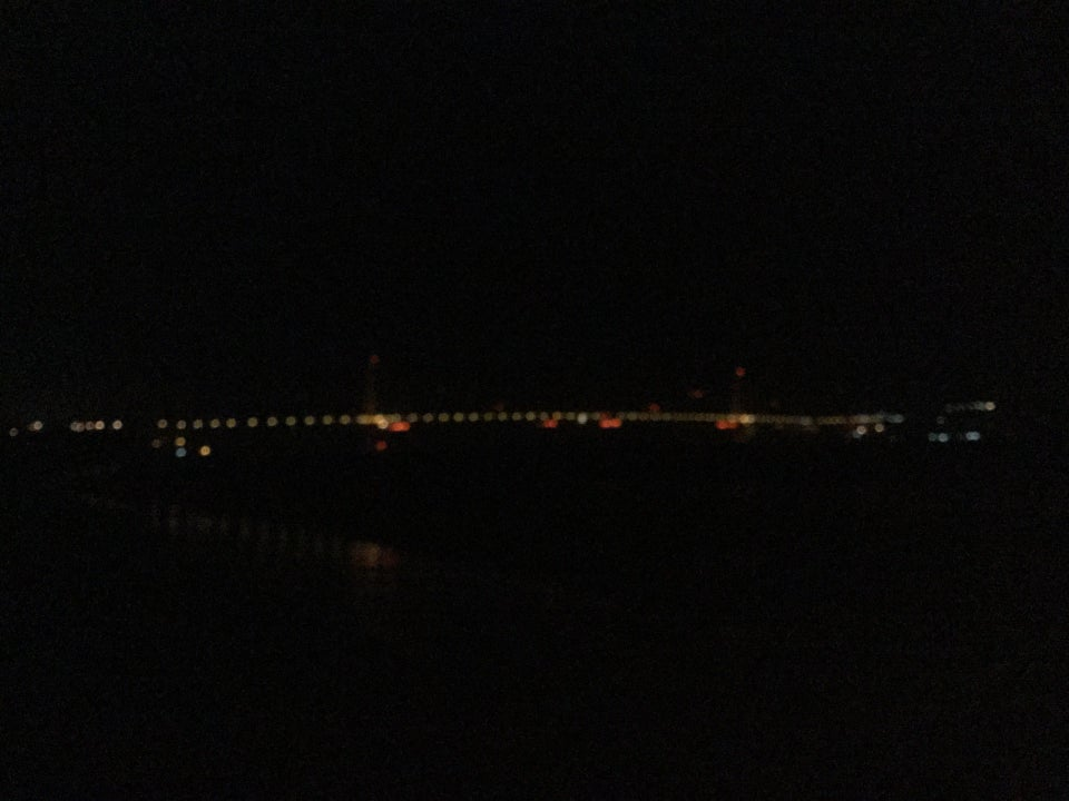 Blurry Golden Gate Bridge lights at night, slightly reflected in the water and waves below of the East Beach