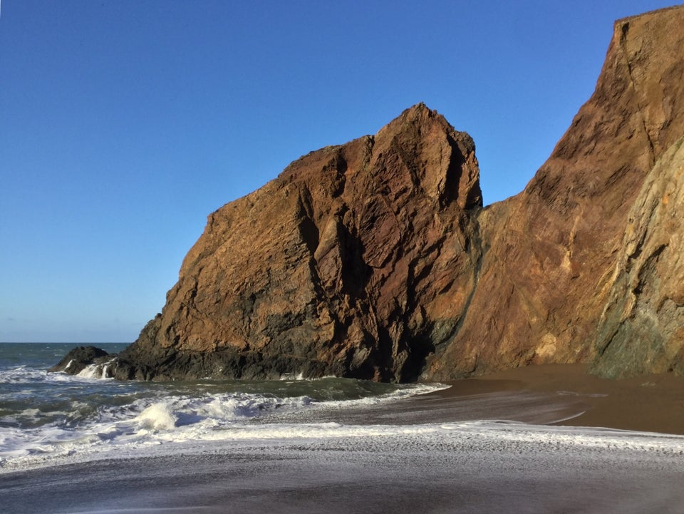 Red rocky outcroppings rising out of the ocean and sand at Tennessee Valley beach