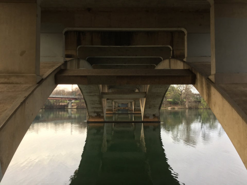 Underneath a bridge, symmetrical concrete support structures, with rectangular arches and supports above greenish water, still enough to reflect the underside of the bridge.