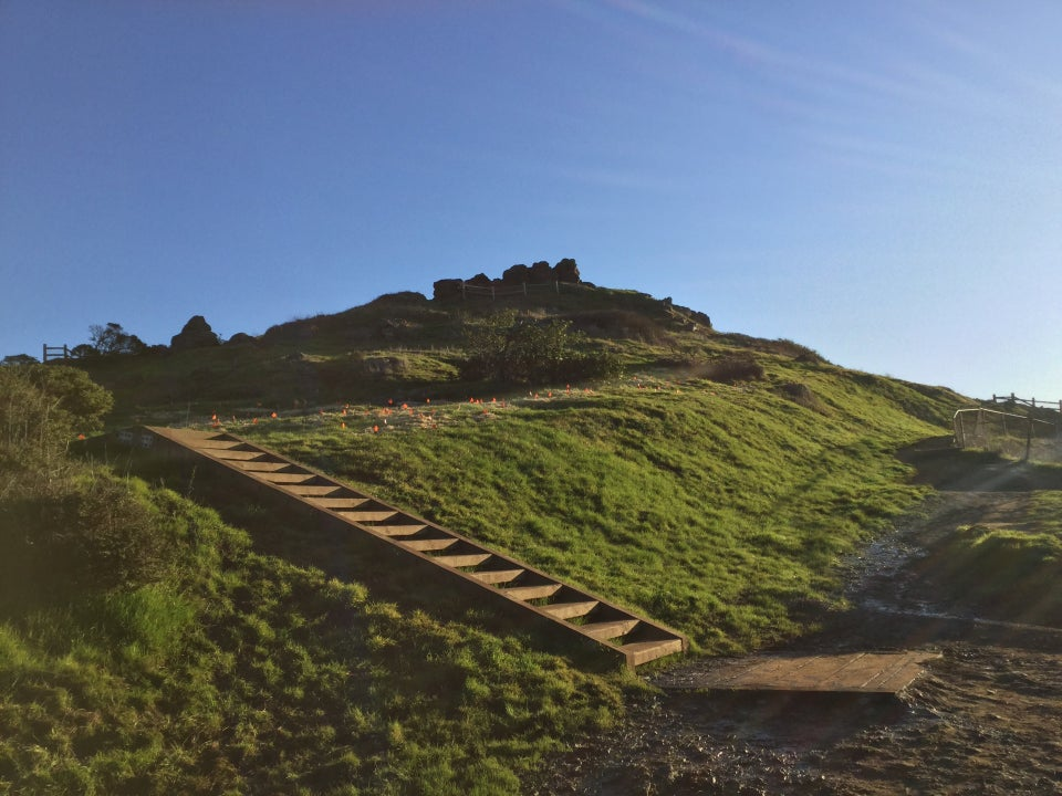 Corona Heights Park, stairs going up and to the left on the green hill with rocky outcroppings on top.