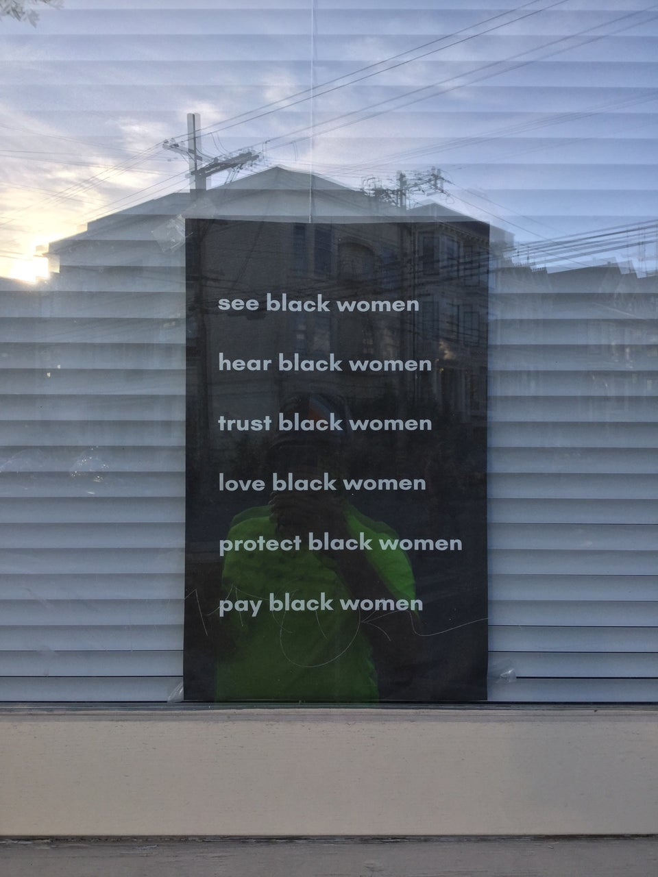 Black sign with white text in a window with white mini-blinds behind it, with six lines: see black women, hear black women, trust black women, love black women, protect black women, pay black women.