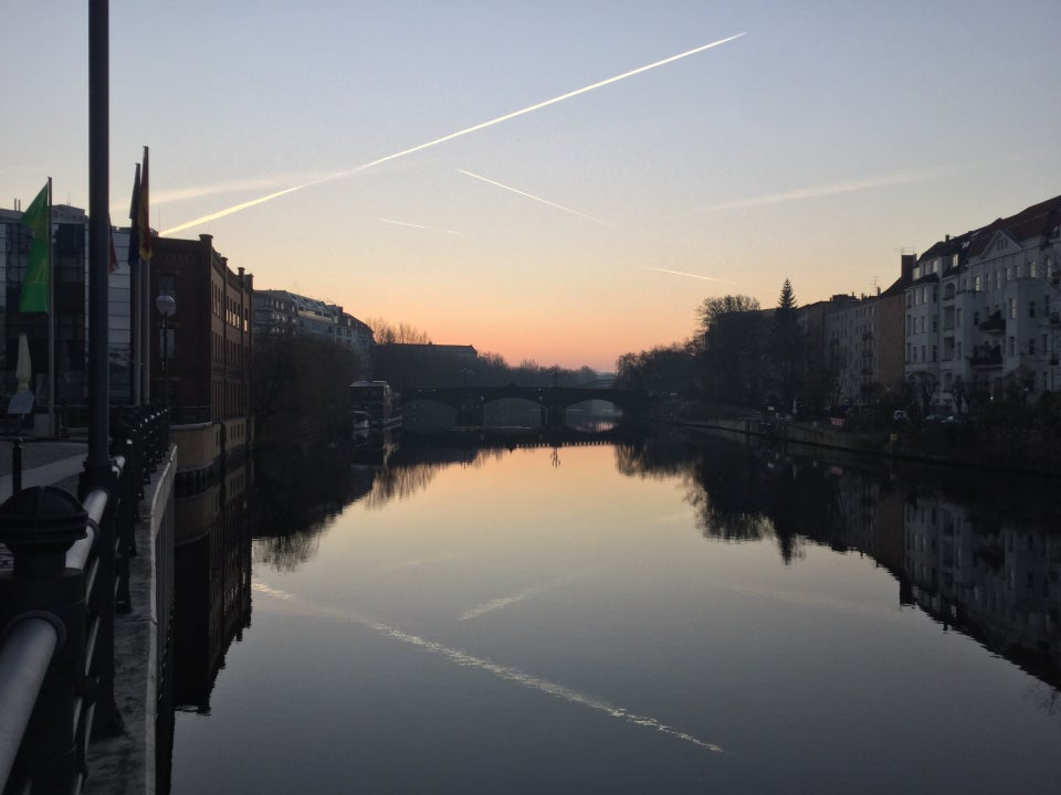 Clear sky with several contrails, orange glow in the middle of the horizon, above buildings on both sides, trees on the right side of the river Spree which is showing their reflections.