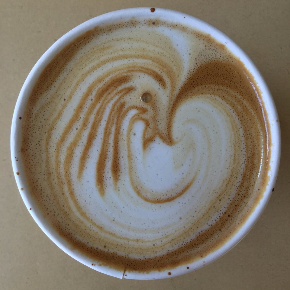 Almond latte with white and brown swirls in a paper cup.