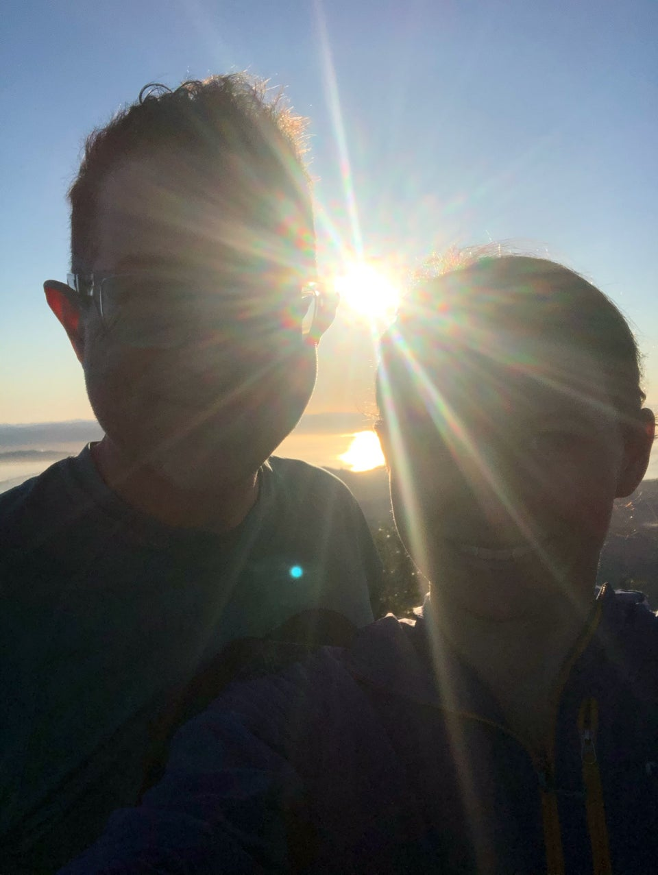 Tantek and Hannah with the sun shining brightly between them, sunbeams across their faces, the bay in the distance glowing with the sun, tiny East Bay hills in the distance.