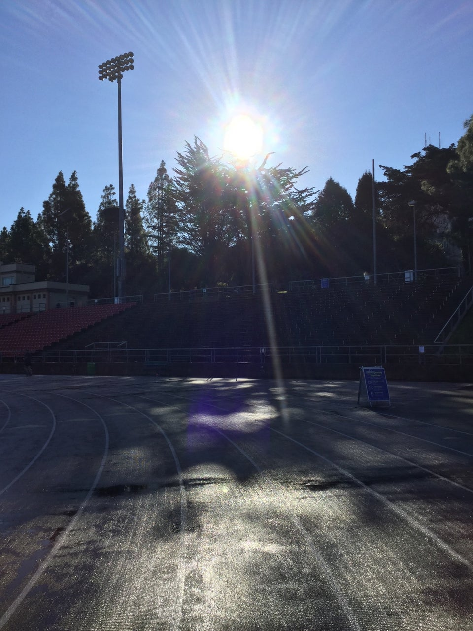 Kezar track rounding the last corner, the sun shining directly overhead lighting up track, a Covid warning placard on the edge of the lanes.