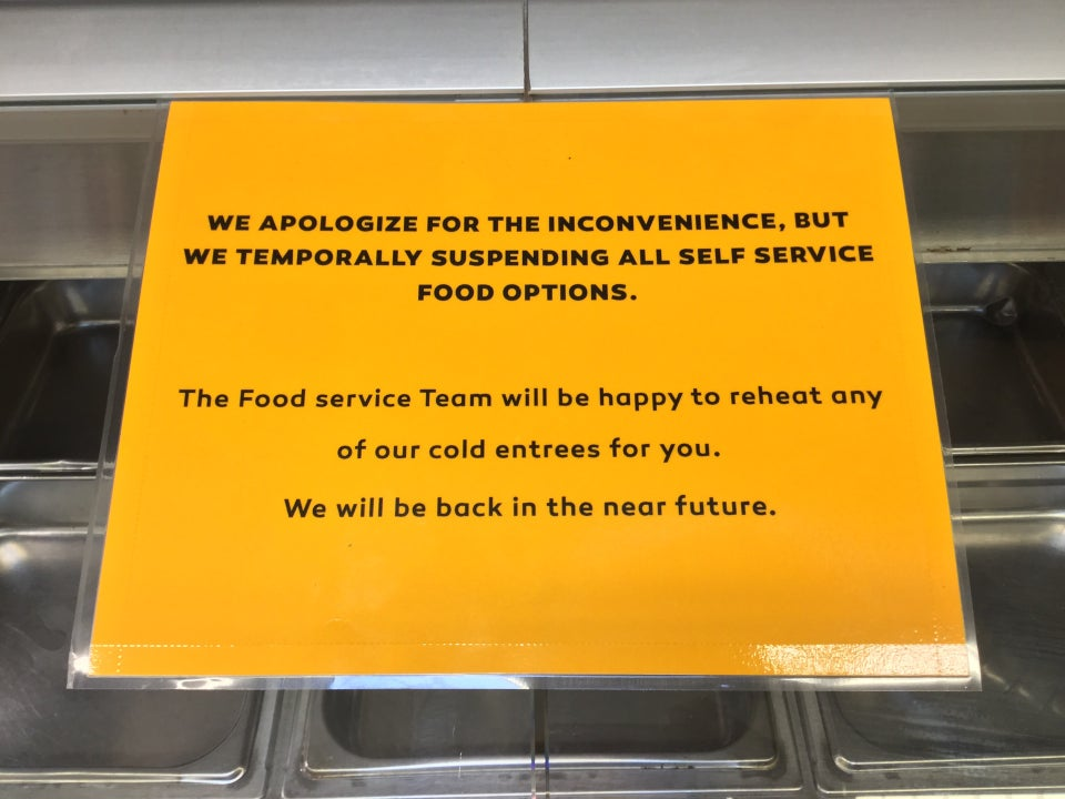 Orange printed sign apologizing for the temporary suspension of self service food options at Haight Street Market, place on top of the sneeze shield over an empty salad bar.