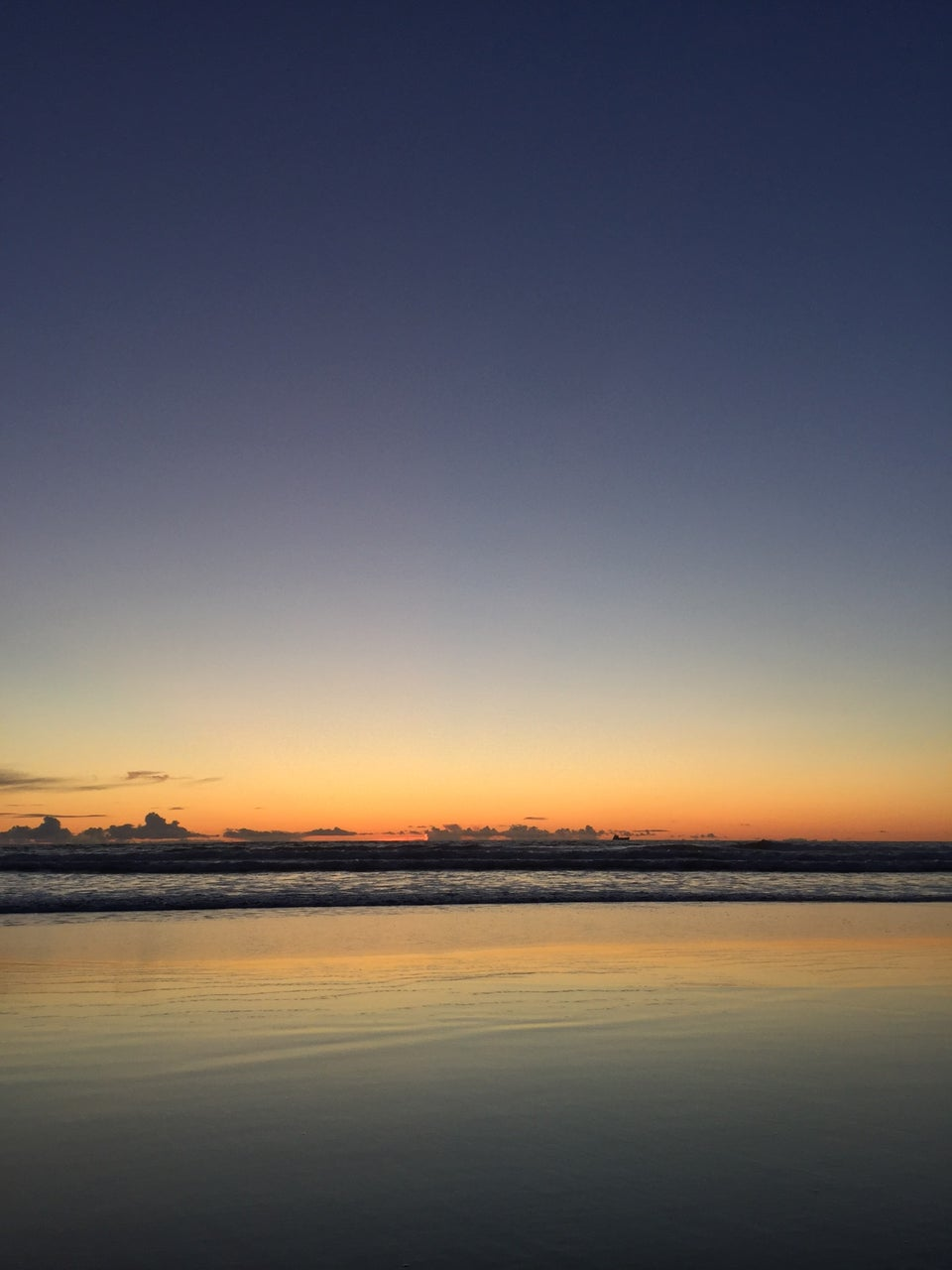 Clear skies just after sunset above waves crashing at Ocean Beach, wet sand reflecting the orange horizon and color gradients in the sky.