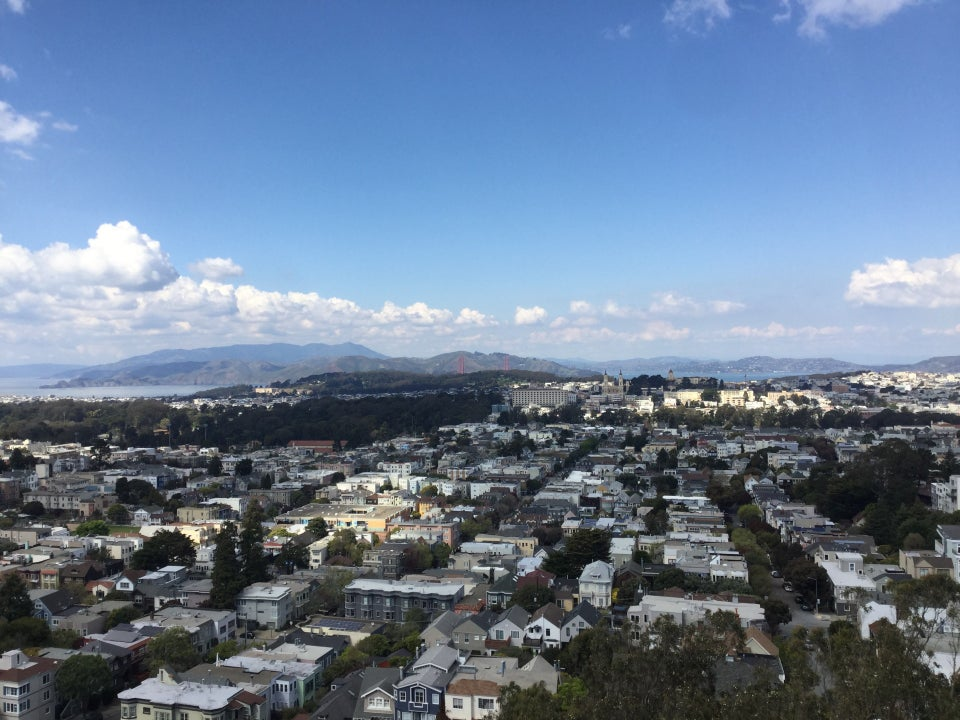 Blue skies with white puffy clouds in the distance over a clear view of Mount Tam, the Marin Headlands, Golden Gate Bridge all in the distance, Golden Gate park and surrounding neighborhoods down below.