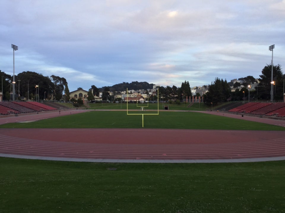Partly cloudy sky above distant trees behind Kezar stadium, two light towers standing tall on opposite sides, bracketing bleachers above the brick red track and green field in the center with yellow football field goals perfectly aligned in the center.