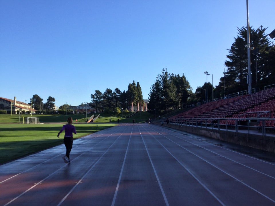Kezar track viewed from lane 5 on the front 100meter segment, lanes 1-3 wet from rain, a runner in lane 2.