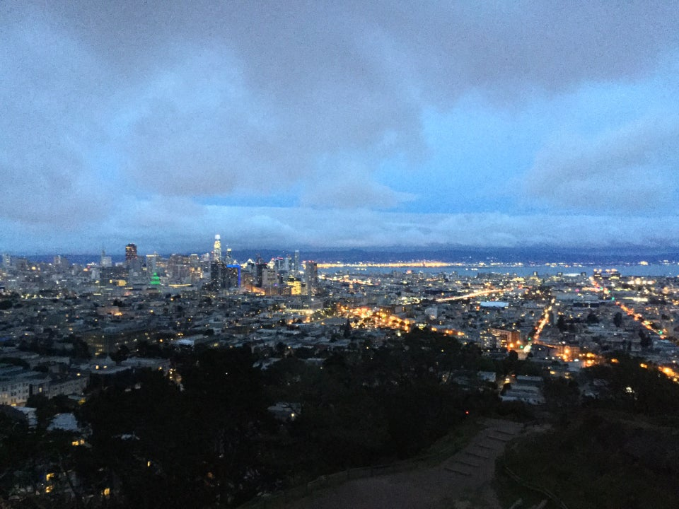 Grey clouds and bits of blue sky above white clouds covering the horizon in the distance above East Bay hills at dusk, downtown San Francisco buildings already lit, City Hall in green, buildings and streets lined with lights, trees below in darkness on the edge of barely visible beige gray trails and dirt area at Corona Heights park below.