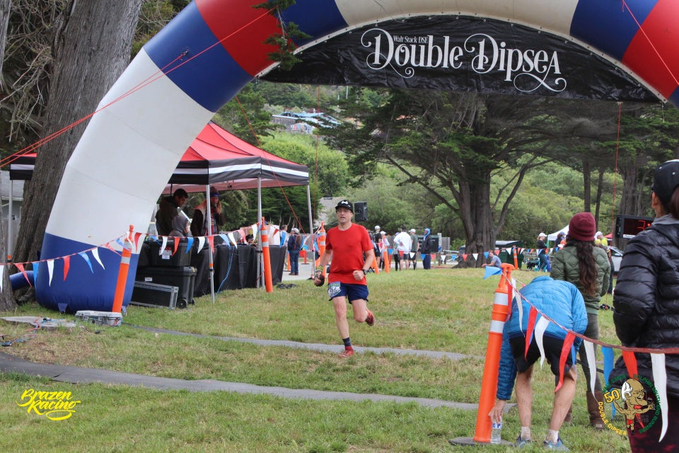 Tantek kicking hard at the Double Dipsea finish line, under a red, white, & blue arch