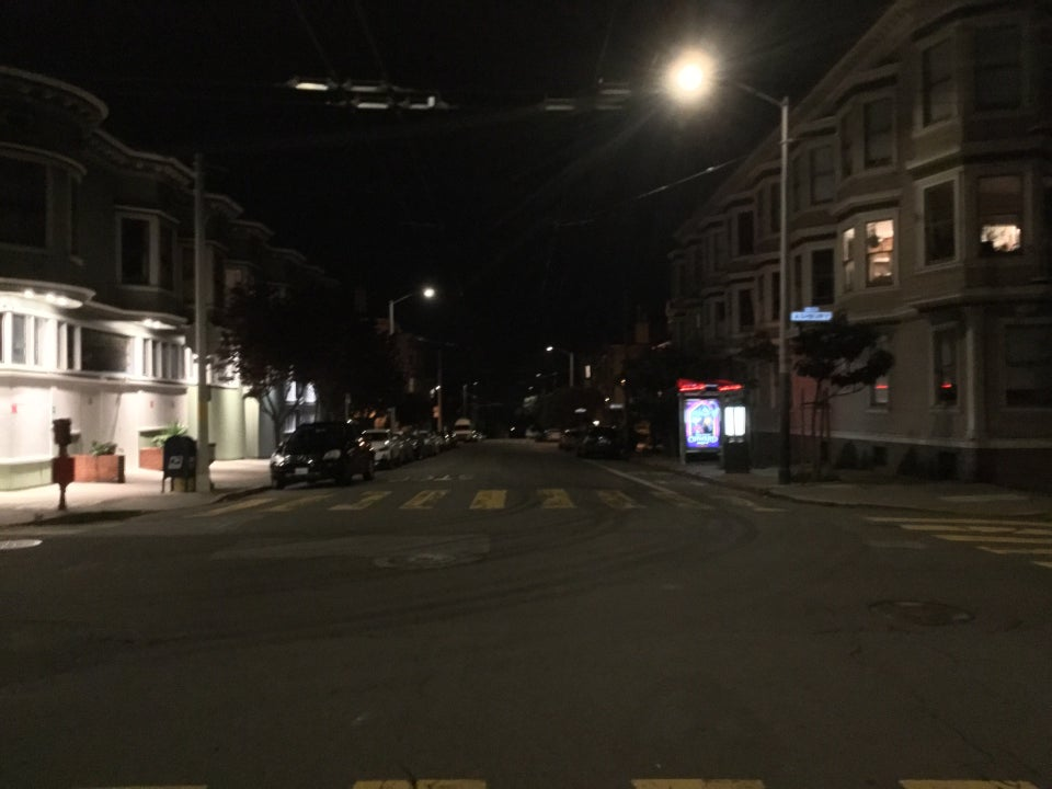 Intersection of Frederick and Ashbury streets at night, looking westward, everything is dark except for streetlamps, lights outside a boarded up Ashbury Market, and a second floor corner apartment on the other side, above a lit bus stop for the number 6 outbound bus.