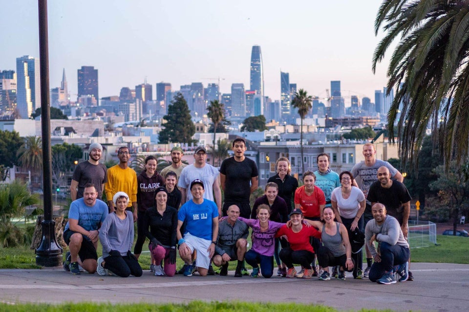 November Project San Francisco group photo in Dolores Park with a view of early morning San Franciso in the background.