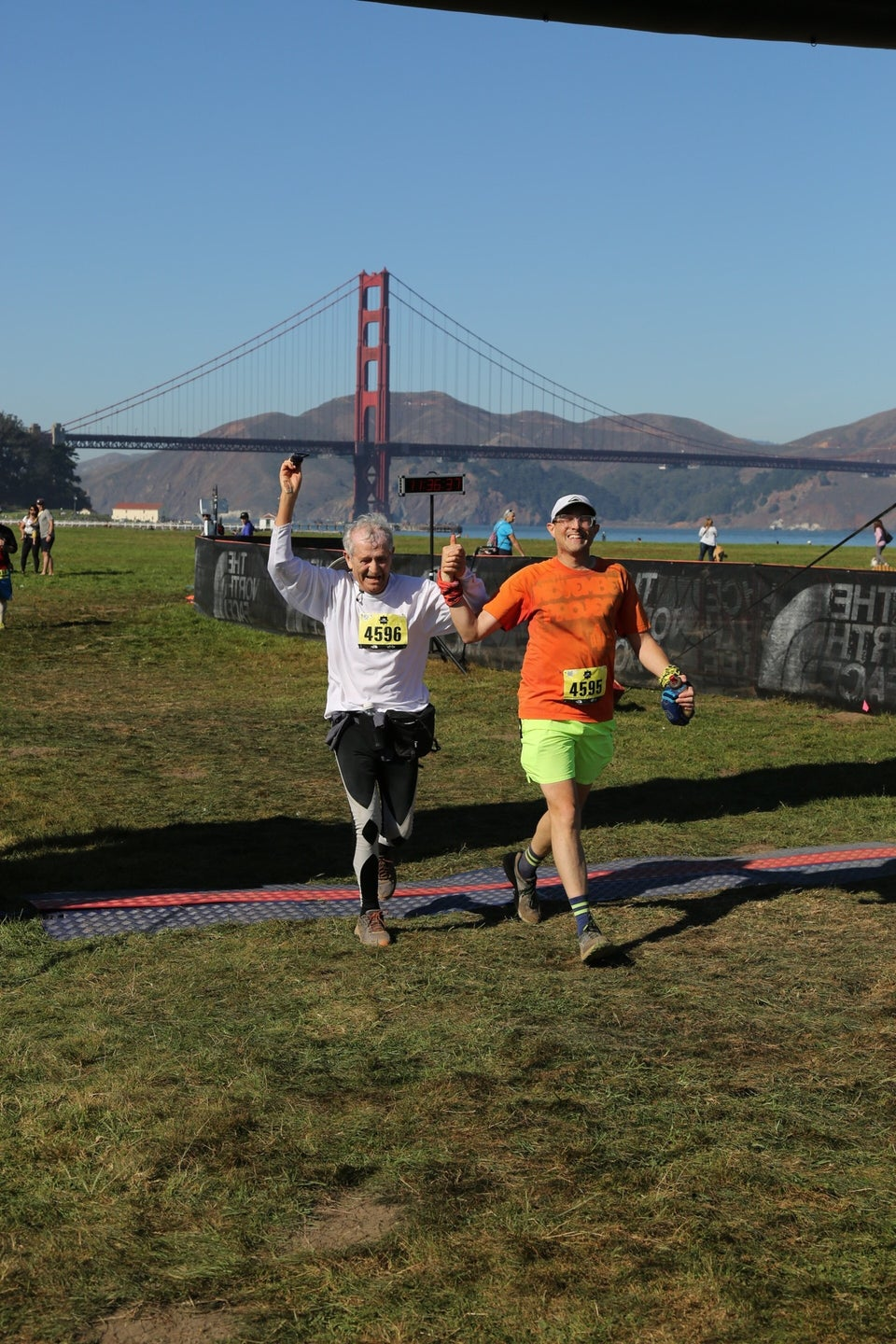 Hasan and Tantek smiling side by side holding raised hands between them, just after they crossed The North Face Endurance Challenge finish line in Crissy Field, San Francisco, with the Golden Gate Bridge and Marin Headlands in the background under a clear blue sky.