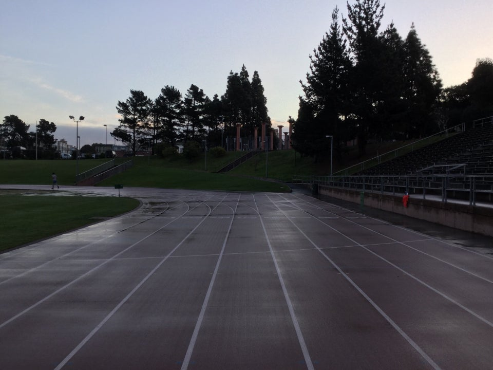 Light blue dawn sky above backlit trees just above the entrance to Kezar Track, as viewed from behind the starting area on the track, looking forward, and the somewhat wet track curving to the left.
