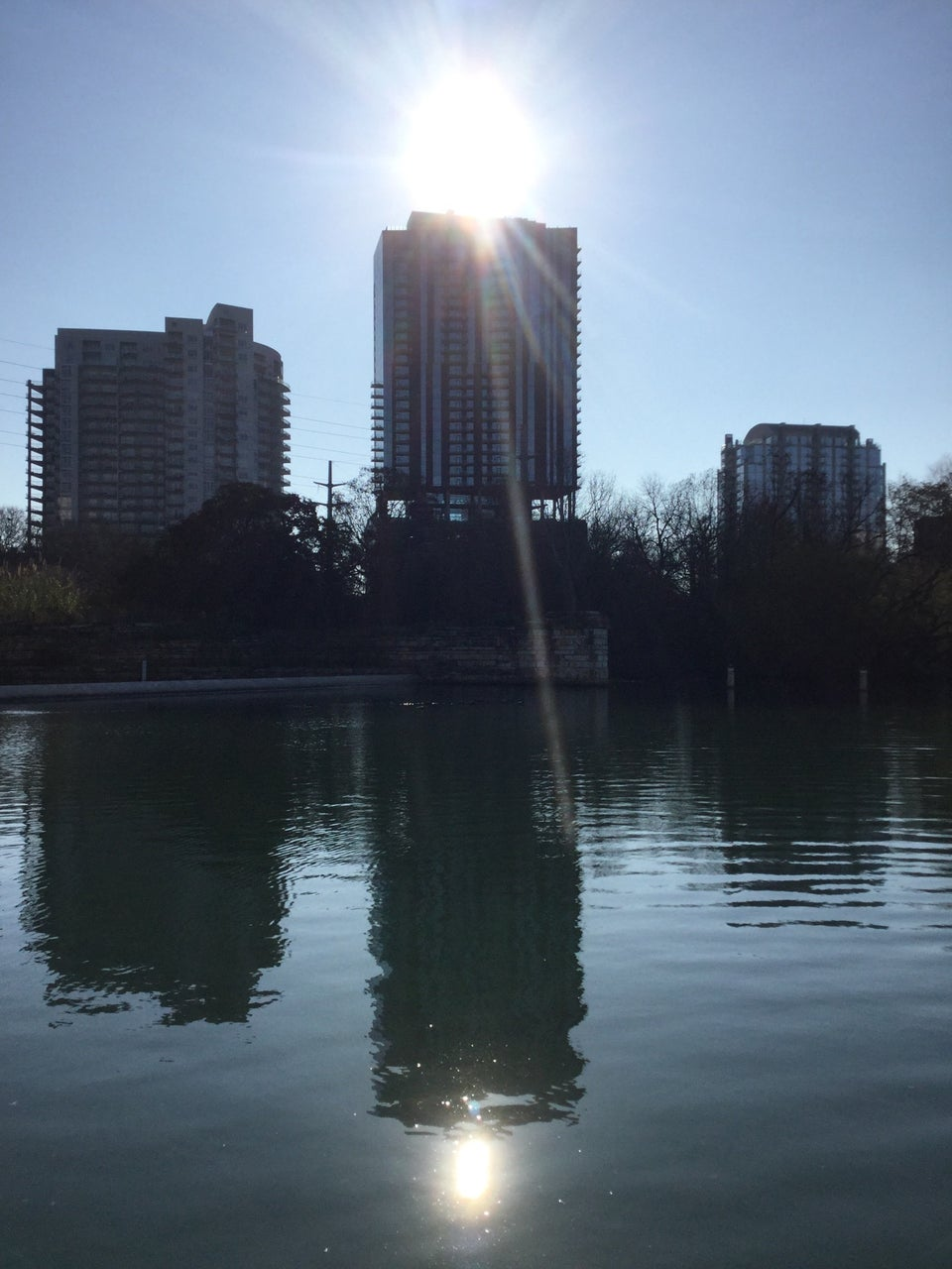 The sun shining brightly in a clear sky over buildings above the river, and reflected in the river as well, in Austin Texas.