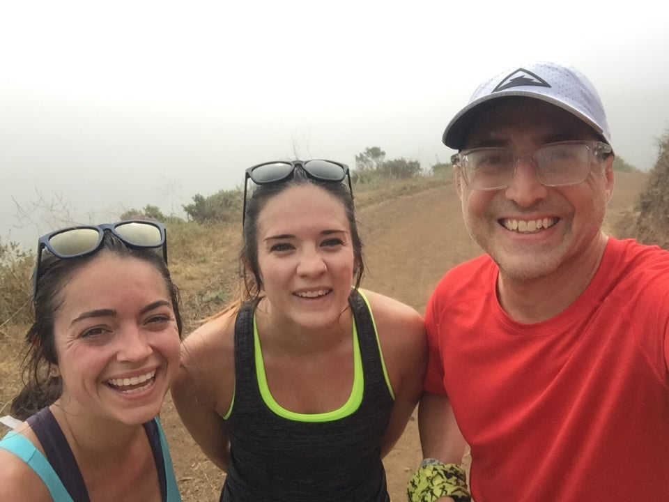 Katie, Morgan, and Tantek on Miwok trail, with nearly nothing visible behind them besides the trail and thick fog, occluding the valley floor and opposite hills