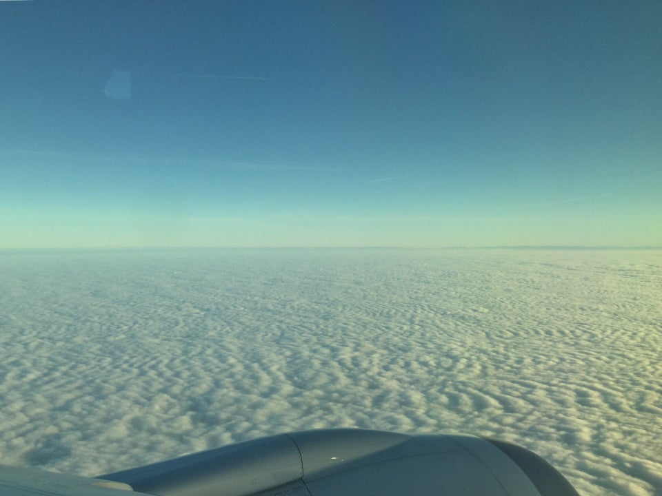 Clear blue sky above a hazy horizon and a blanket of clouds, the top of a jet engine just visible in the lower sixth of the photo.