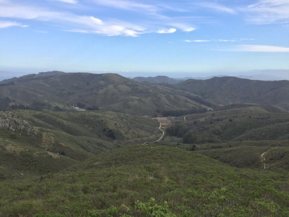 Blue sky with a few thin scattered clouds above Tennessee Valley and the green hills behind it, and in front of it as viewed from Coyote Ridge.