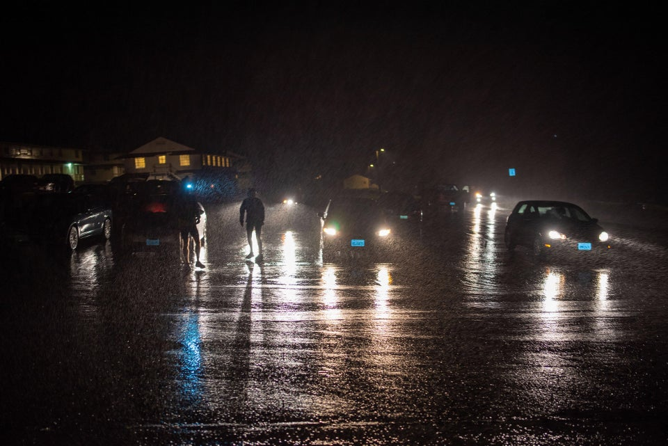 Several cars parked at and a few more approaching the Rodeo Beach parking lot, a couple of buildings in the background lit from inside, silhouettes of a few people backlit by headlamps reflecting on the wet asphalt in the dark.