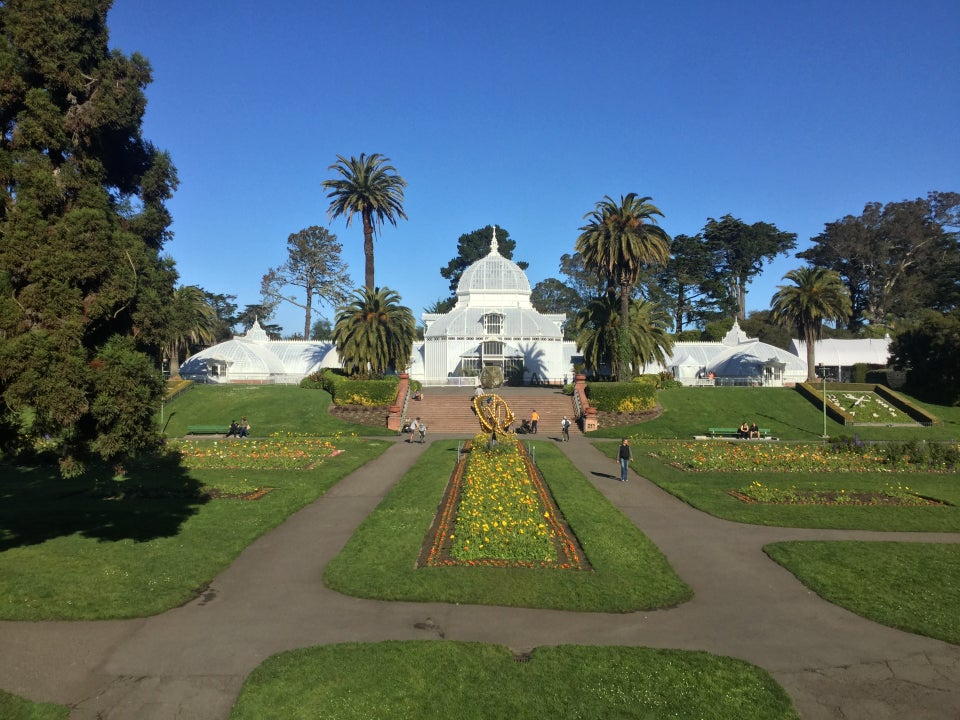 Conservatory of Flowers building in Golden Gate Park under a clear blue sky, with flower beds, lawns, and paths in the foreground.