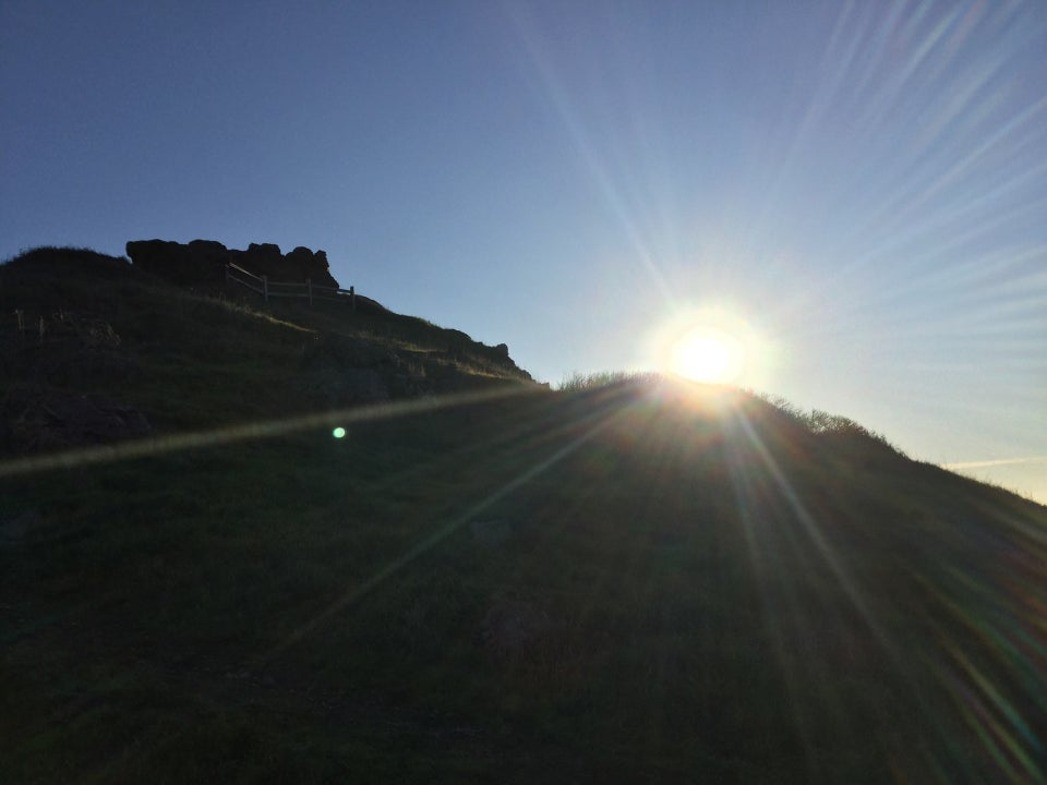 Sun rising behind Corona Heights hill with sunbeams emanating in all directions, lighting up the backlit hill.