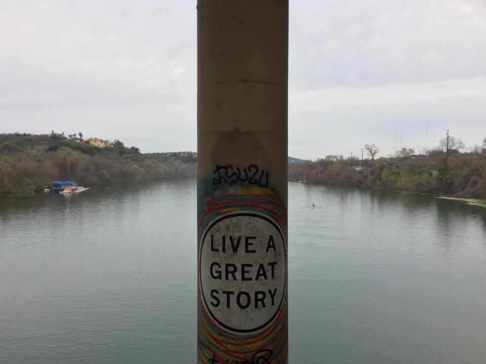 Artwork, black all capitals text on a white disc background, saying LIVE A GREAT STORY, on a tall concrete post of a bridge, the waters of the lake behind it, as well as trees on both shores.