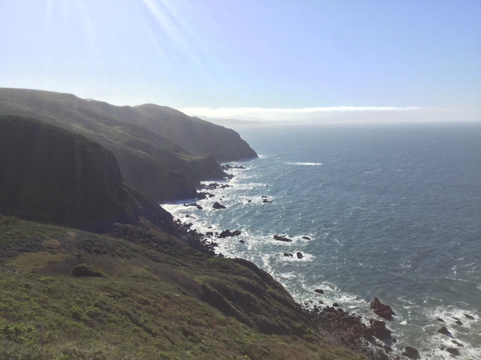 Clear blue sky above the Marin Headlands and Pacific Ocean, looking south to Pirates Cove below, the rocky shore breaking up waves with white froth.