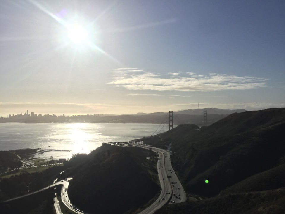 The sun shining brightly above San Francisco, reflecting off the bay, the Marin Headlands in the foreground, Golden Gate bridge towers emerging from them on the right.