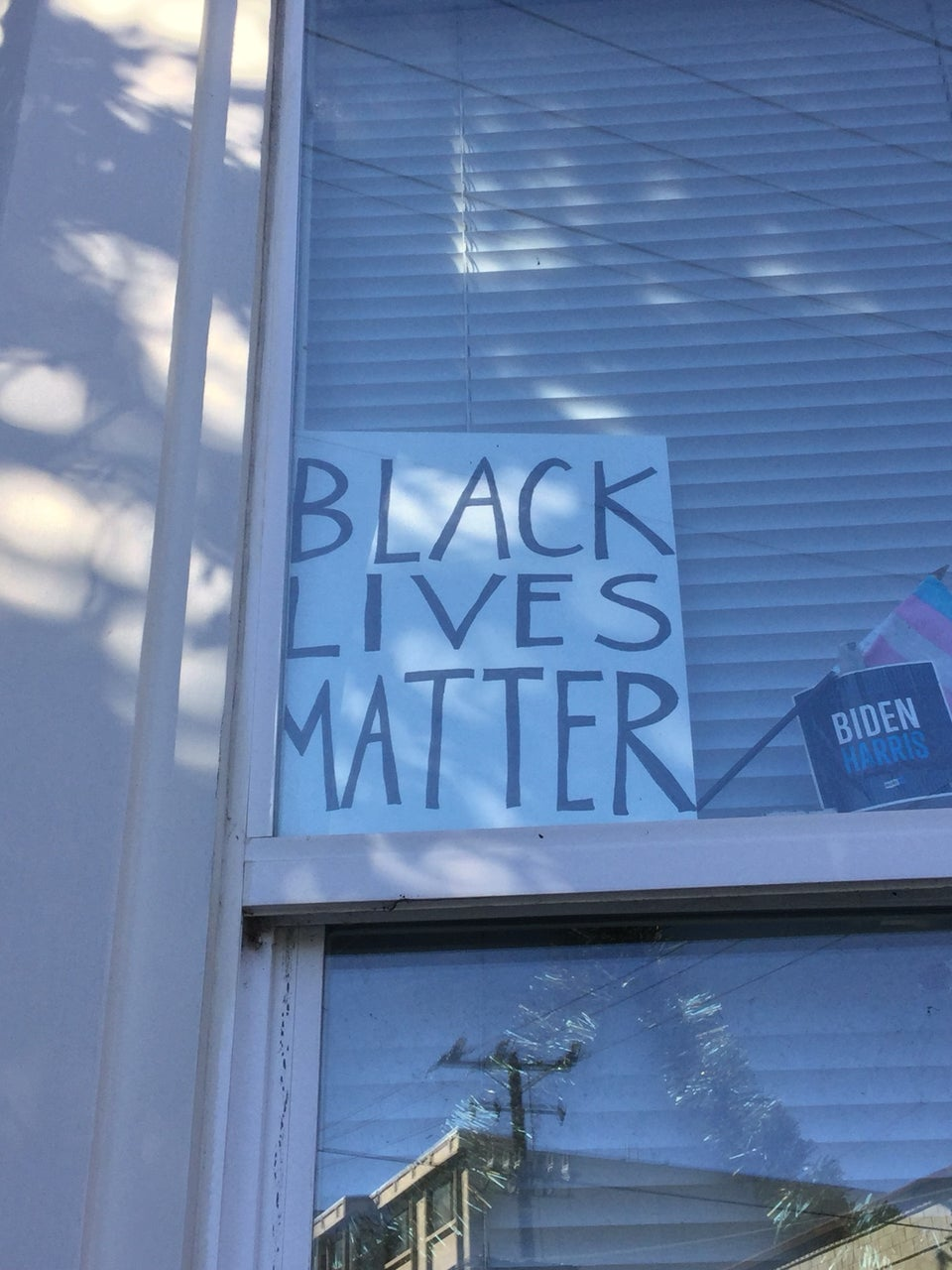 Hand drawn BLACK LIVES MATTER sign, black marker on white cardboard, inside the window of a building, mini-blinds closed behind it holding it up, a small BIDEN HARRIS sign next to it.