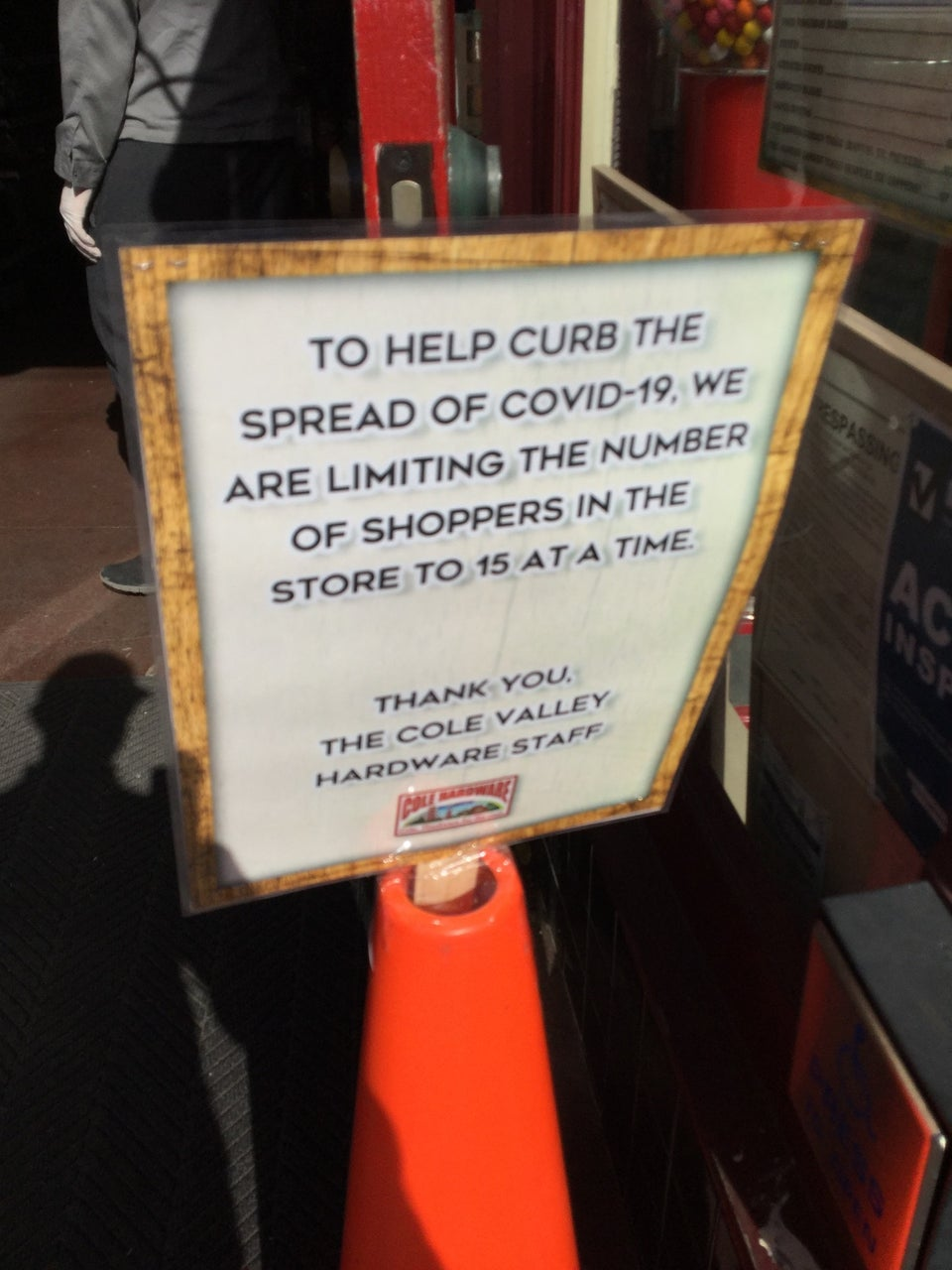 Sign in front of a store entrance with text TO HELP CURBE THE SPREAD OF COVID-19, WE ARE LIMITING THE NUMBER OF SHOPPERS IN THE STORE TO 15 AT A TIME. THANK YOU, THE COLE VALLEY HARDWARE STAFF.