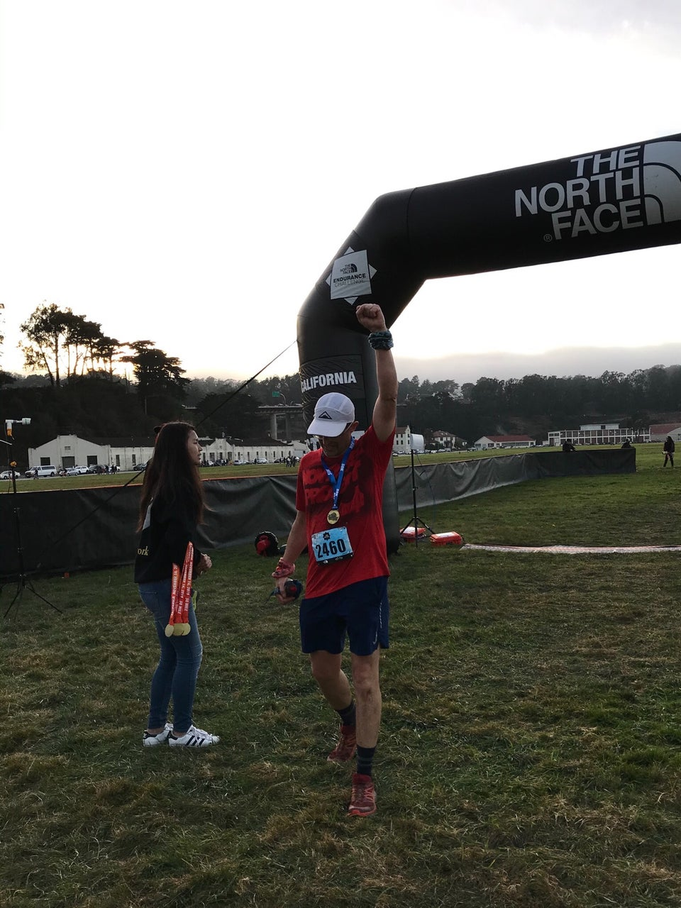 Tantek wearing a 50k finisher's medal just past the The North Face Endurance Challenge finish line in Crissy Field, San Francisco, bowing his head, raising his left fist to the sky.