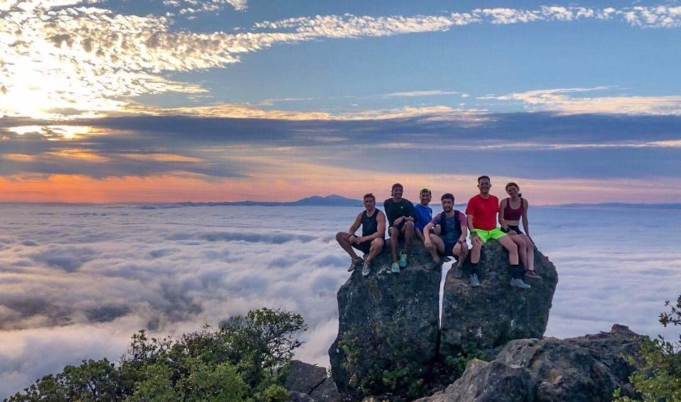 Trail runners perched on a rocky outcropping on top of Mt Tam, above the clouds, Mt Diablo in the background, the sun rising through the clouds
