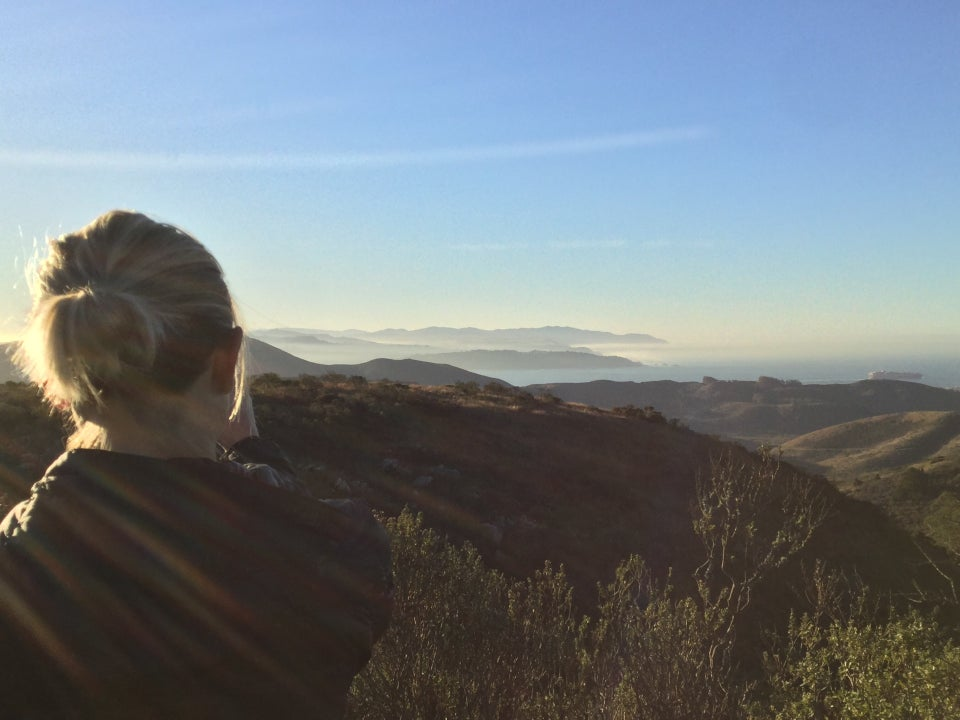 Emily taking a photo, distant hills, haze, the Pacific Ocean, and Marin Headlands.