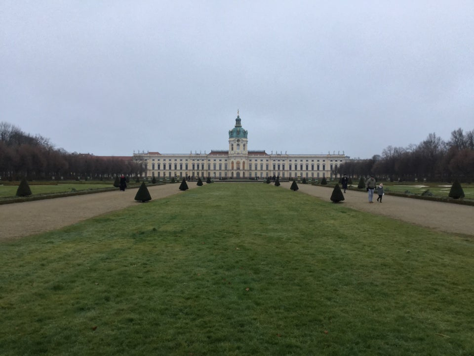 Castle Charlottenburg with a green field in front, overcast skies overhead.