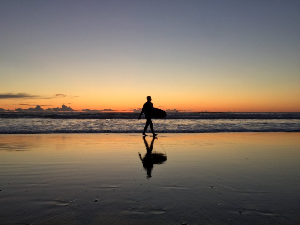 A surfer walking out of the surf with their surfboard tucked under their arm, just after sunset, clear skies, yellow orange horizon over the ocean, wet sand reflecting the sky and surfer.
