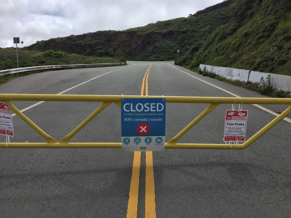 Yellow barricade across the North entrance to Twin Peaks, with a large sign posted in the middle of it saying CLOSED with additional details.