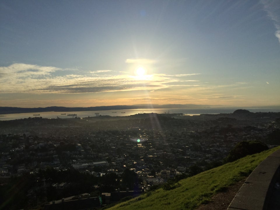 Sunrise just above low hazy clouds, clear sky above, reflecting off the bay and glinting off building windows, nearby green grasses on the side of the Twin Peaks.