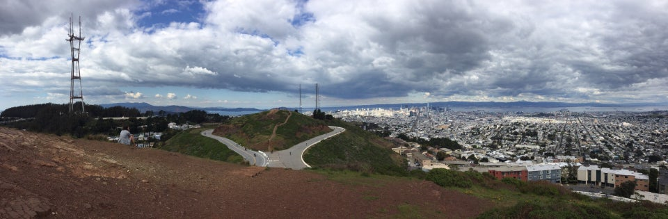 Panoramic photo of the view from Twin Peaks South Peak of Sutro Tower, distant Marin hills, the Golden Gate Bridge, downtown San Francisco, neighborhoods, East Bay hills, the bay with tiny container ships and the the idling Grand Princess.