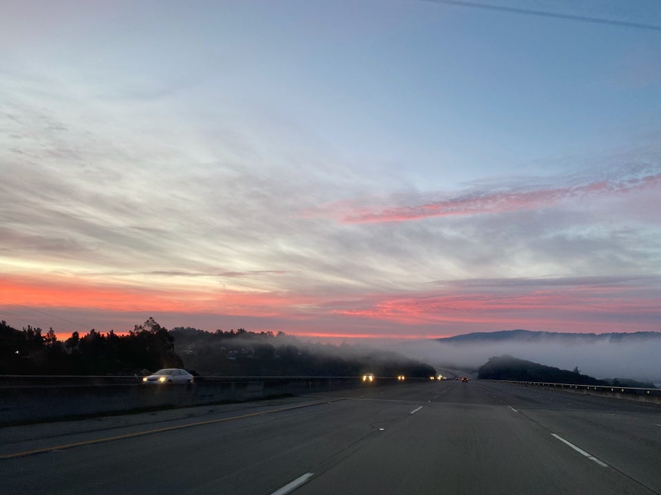 Light purple to blue sky above horizontal streaks of cotton candy pink and orange clouds above distant trees, a low fog, and mountains, driving down highway 280 with very few cars on the road.