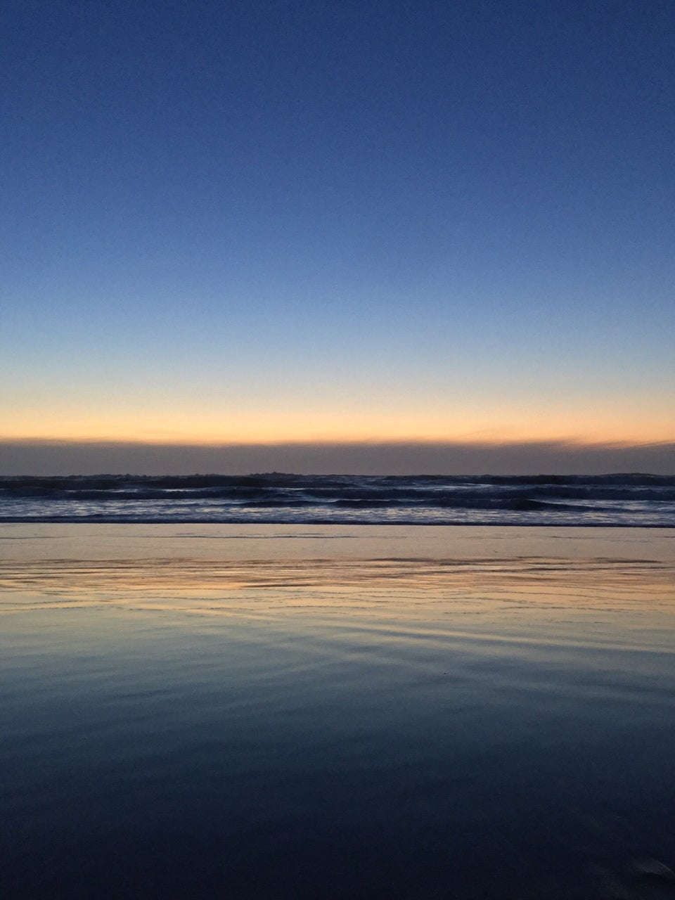 Medium to light blue gradient of sky above an orange glowing horizon over low clouds, waves crashing below them, wet sand reflecting the orange glow and blue sky.