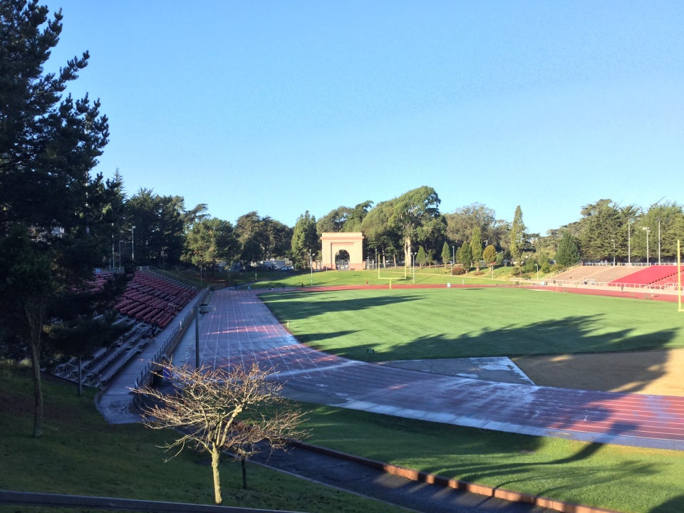 View of Kezar Stadium from the entrance, clear blue sky above, wet track below with almost no runners.