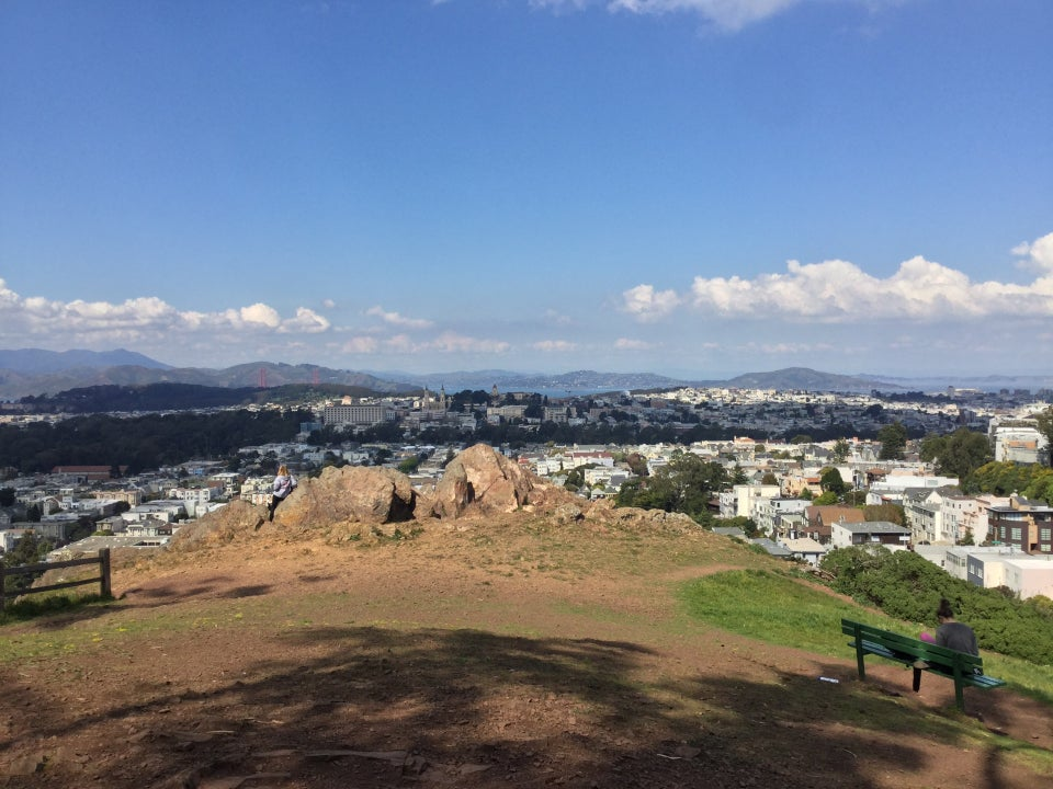 Northward view of Tank Hill Park with Marin hills, Golden Gate bridge, and Angel Island in the distance, largerocks and the bench at Tank Hill park in the foreground with one woman at each.