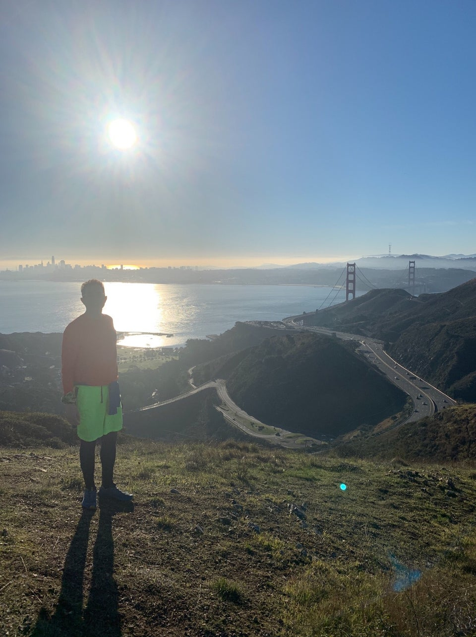 Tantek standing on a hill, backlit by a bright sun in the blue sky, the San Francisco skyline and bay behind him, Golden Gate bridge towers visible behind the Marin headlands to the right, the 101 freeway far below, sparse with tiny cars.