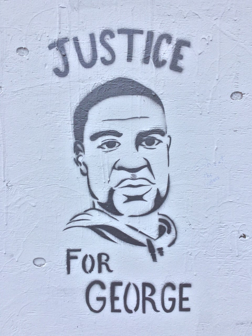 Stencil street art of George Floyd on a gray wall with the word JUSTICE above his head, and FOR GEORGE below. Two of the dried drippings of gray paint appear as if they are tears coming from his right eye.