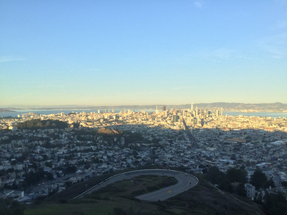 View of sunset-lit downtown San Francisco in the distance as viewed from Twin Peaks, with the hairpin turn below, and immediately below the green hill slope of Twin Peaks summit.