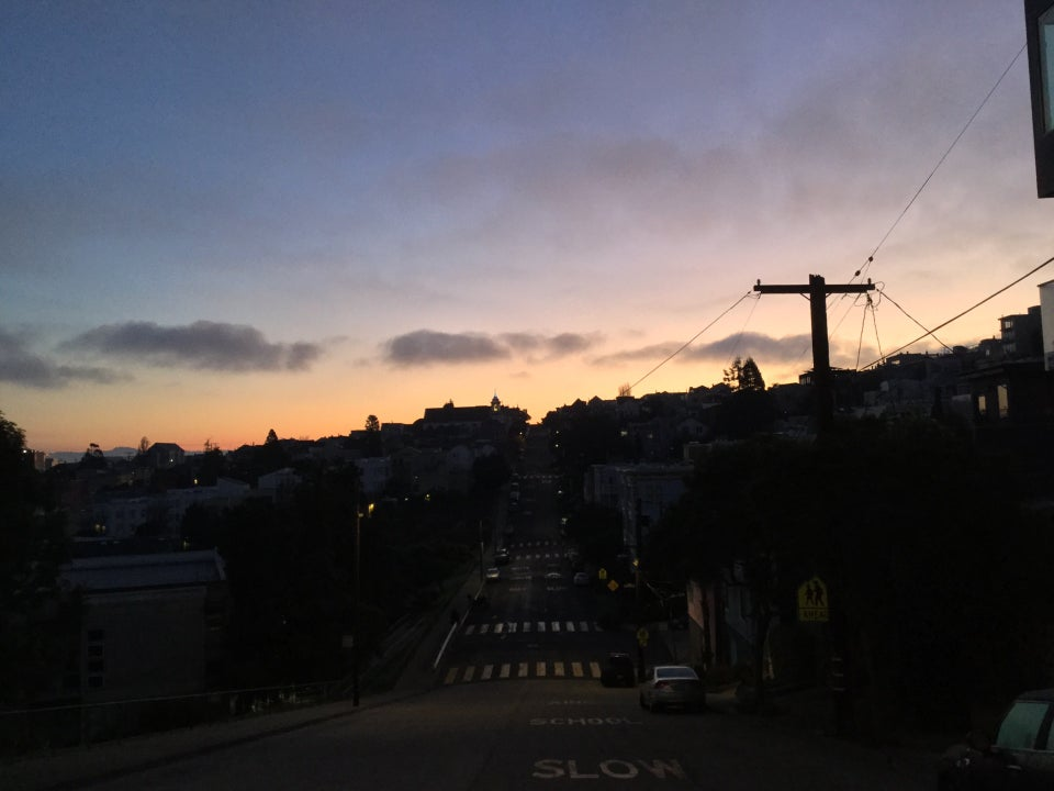 Looking down a street in Potrero hill that dips down and goes back up, at dawn with a purple blue sky that turns orange at the horizon, backlighting the outline of buildings and a telephone pole.