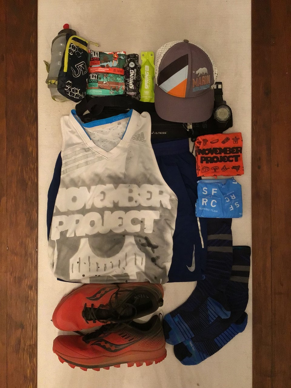White yoga mat on a hardwood floor with running shoes, clothes, gear, fuel laid out in an orderly fashion.